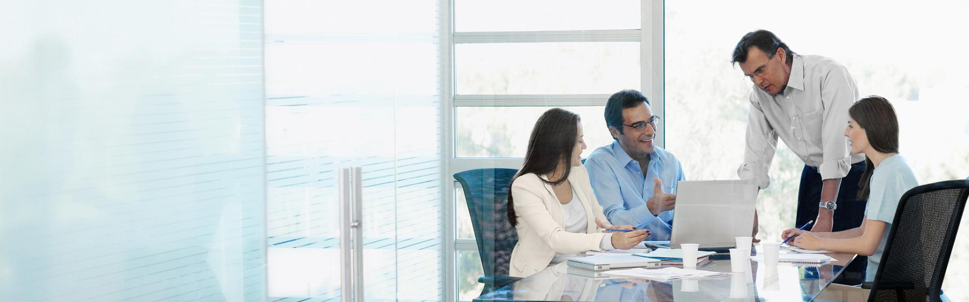 Executives using SAP insurance software in a meeting