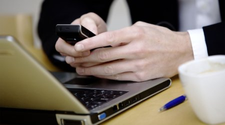 Businessman messaging on mobile device at work