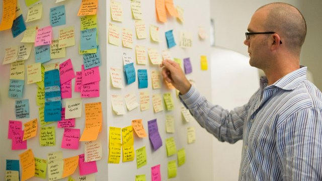 Businessman organizing sticky notes on wall