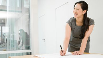 Businesswoman smiling in room during process orchestration discussion