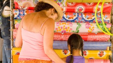 Mother and daughter looking at colorful textiles