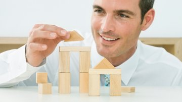 Businessman building a wooden structure