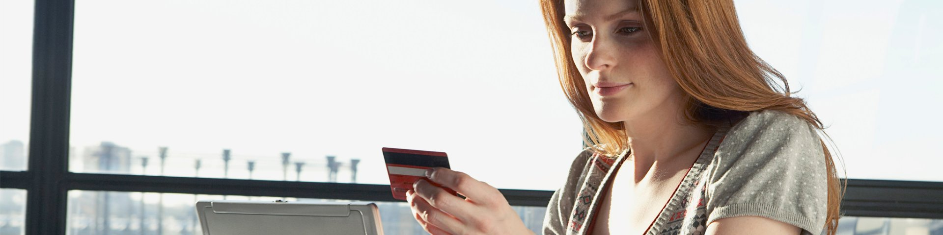 Woman holding credit card and laptop, shopping at an etail store