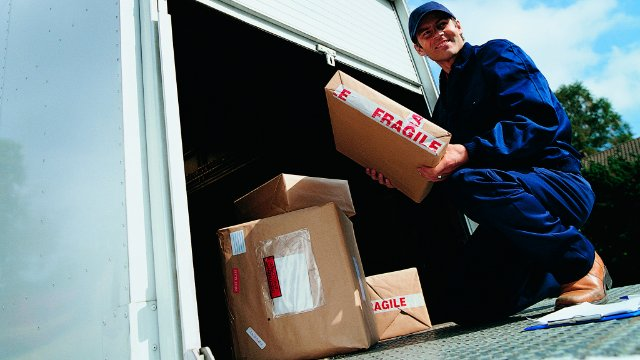 Delivery man removing packages from truck