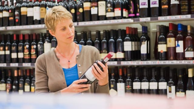 Shopper reading a wine bottle label