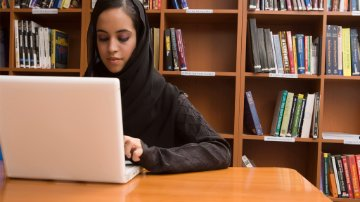 A female student working on her laptop in the library