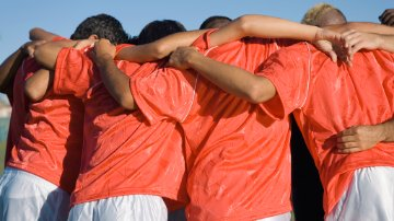 Soccer team supporting each other in a huddle