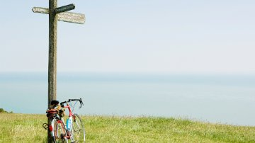 Bike leaning on a signpost by the sea