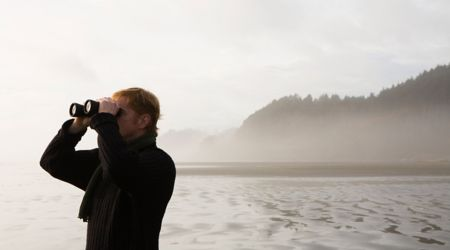 Man standing on empty beach, using binoculars