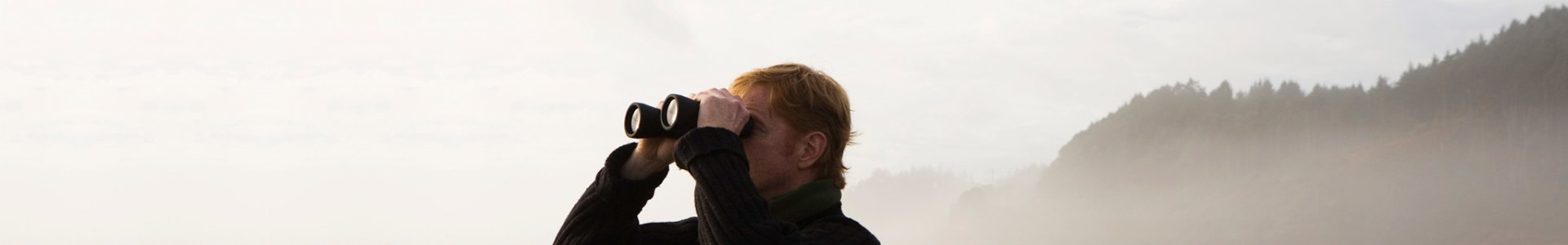 Man looks through binoculars to detect cyberattacks