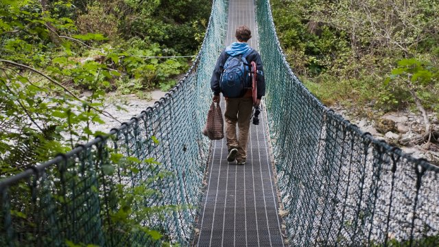 Man walking across a suspension bridge