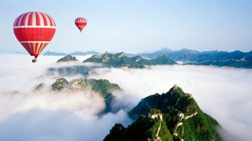 Hot air balloons flying over a mountain summit