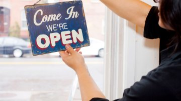 Retailer holding an open sign