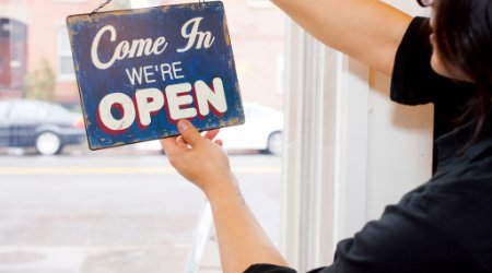 Woman flipping over open sign in cafe
