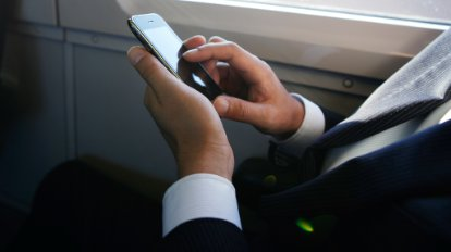 Businessman accessing data on a mobile device while traveling on a train