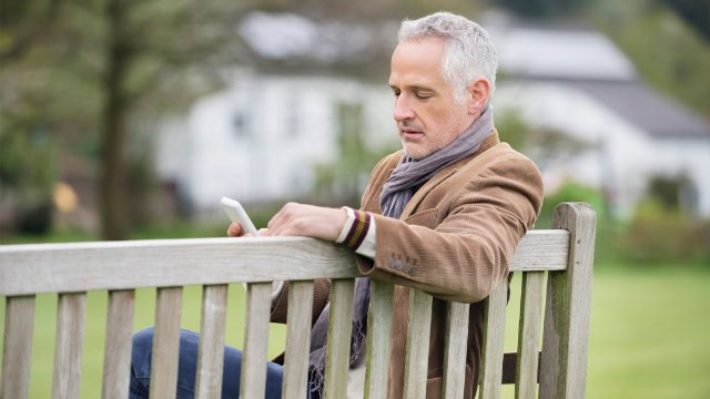 Man on a bench checking test data management and migration reports on his mobile device