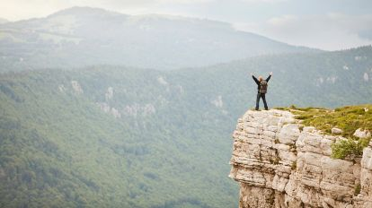 Photo of a person standing on a cliff overlooking mountain peaks, representing success with master data management