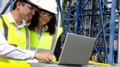 Chemical plant workers accessing SAP training tools on a laptop