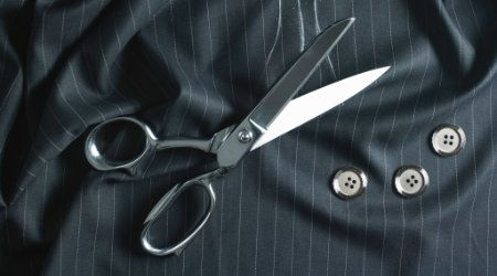 Tailor shears on pinstripe wool fabric