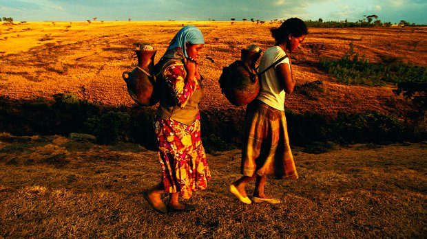 Women carrying water jugs in Africa