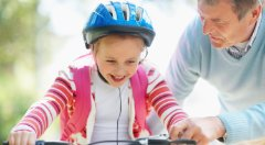 Child learning to ride bike with father