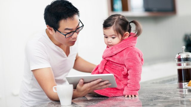 Father and young girl looking at mobile tablet