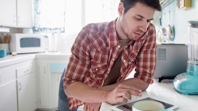 Man using tablet pc in kitchen