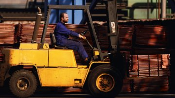 Employee operating a forklift in a lumber yard