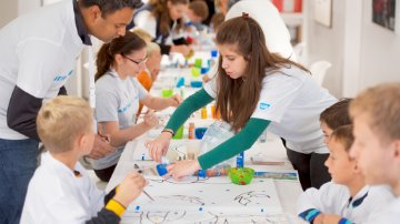SAP volunteers helping children with crafts