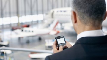 A&D executive using a smartphone in a hangar