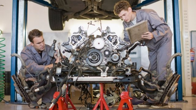 Mechanics working on a car engine