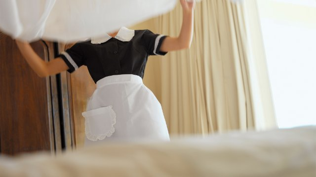 Maid changing the bedding in a hotel room