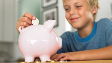 boy looking at piggy bank
