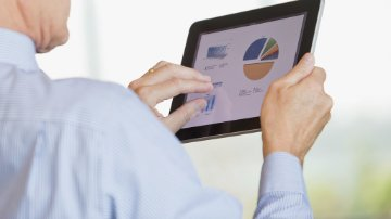 Man viewing financial report on tablet