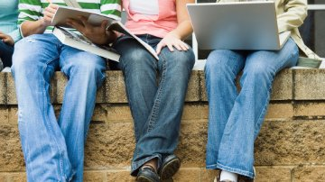 App developers sitting on a wall with textbooks and a laptop