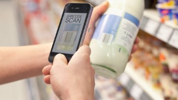 Close-up of cell phone scanning bottle in supermarket