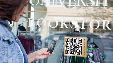 Woman scanning a QR code from a shop window