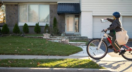 Bicyclist delivering paper to a house