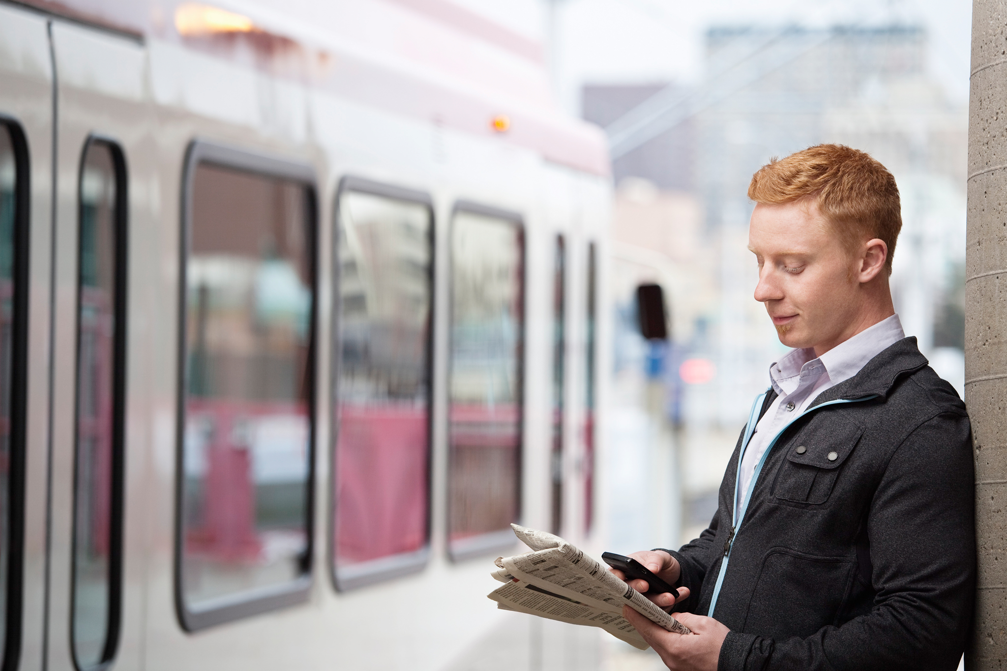 man reading paper near train