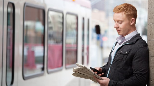 Commuter using a smartphone on a train platform