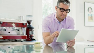 Man using a digital tablet in his kitchen