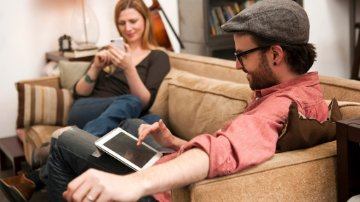 Couple sitting on a sofa using a digital tablet and smartphone