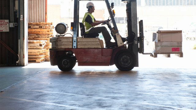 Warehouse worker transporting goods on a forklift