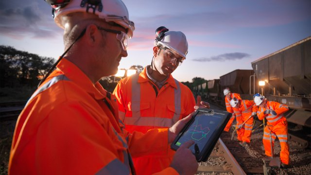 Railway workers using digital tablet to view work details on railway tracks