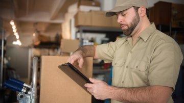 Delivery man in warehouse holding portable information device
