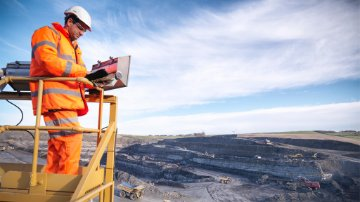 Ecologist using digital tablet surveying surface coal mine site from platform