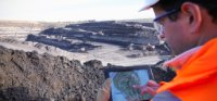 Worker using a tablet at a coal mine