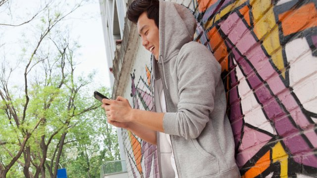 Young man leaning again a wall covered in graffiti and texting on his phone, skateboard is next to him