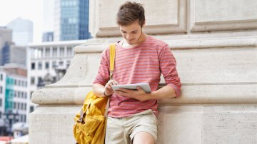 Male student using a tablet computer in a city
