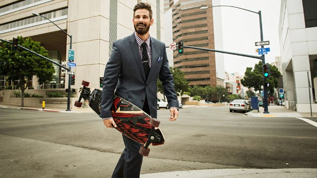 Young businessman who works for a tech startup carrying skateboard and crossing street